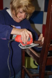Artist Toni Mason, owner of Sew Crafty in Durham, works on sanding her chair at the artist workday held at The Scrap Exchange on February 5th.