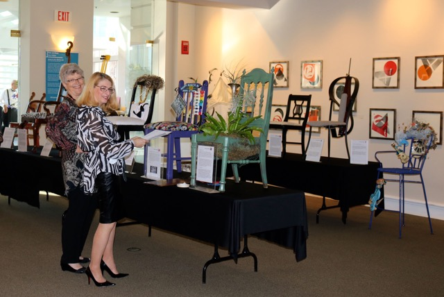 Kathy Silbiger and Ellen Ciompi prepare some of the musical chairs for        exhibition in the Allenton Gallery on March 5.